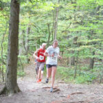 Two people running through woods