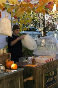 Ben Madey of Maple Leaf Sugaring is shaping a batch of maple cotton candy for a customer at his stand at Hawthorne Valley's Fall Festival
