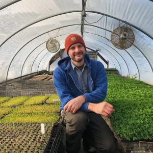 Hawthorne Valley Farm's Vegetable Grower Todd Newlin sitting in the greenhouse surrounded by lettuce starts