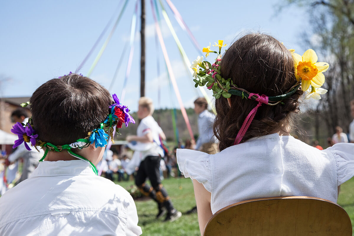 Students wearing flower crowns watch May Pole dancing. Photo by Catdodge Photography.