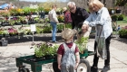 Couple shops for plants stopping to chat with a small child at May Day celebration. Photo by Catdodge Photography.