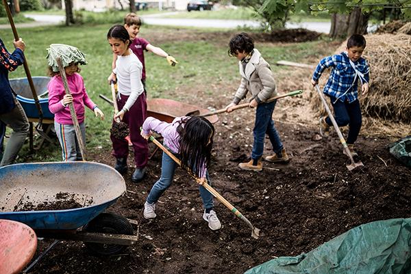 school children working together to shovel compost